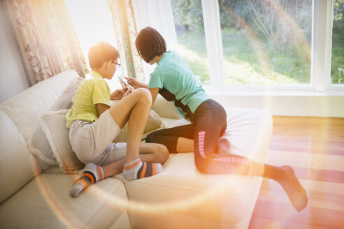 Mixed Race brother and sister texting on cell phone near window - BLEF04546