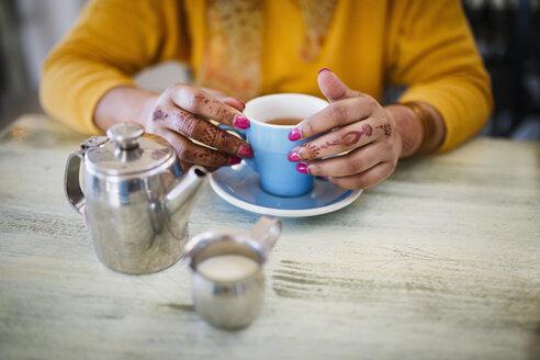 Woman with henna tattoo on hands drinking tea - BLEF04555