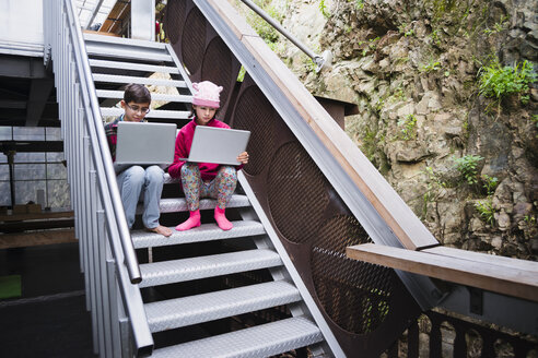 Mixed Race brother and sister sitting on staircase using laptops - BLEF04561