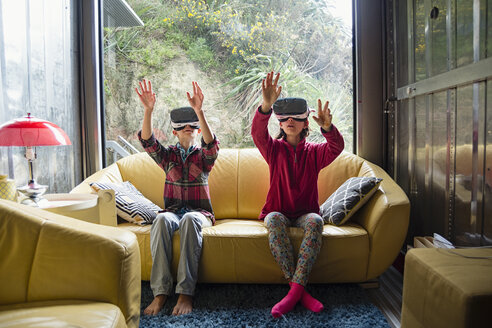 Mixed Race brother and sister using virtual reality goggles on sofa - BLEF04564