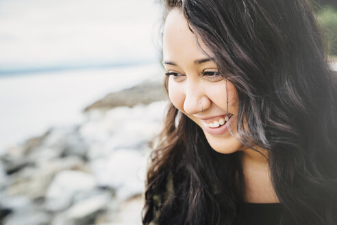 Smiling Mixed Race woman at ocean - BLEF04579