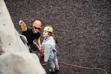 Caucasian man and woman pointing at rock climbing wall - BLEF04594