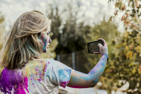 Gir Holi powder colours in her face, taking selfie, Germany - VGPF00038