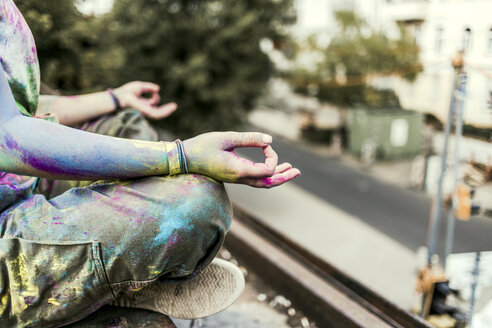 Girl with Holi colours on her clothes sitting on bridge, meditationg, Germany - VGPF00044