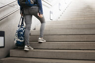 Woman with bag and backpack walking up stairs at the station - HMEF00409