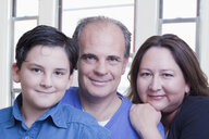 Hispanic father and wife posing with son - BLEF04646