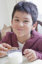 Hispanic boy eating cookie with milk at table - BLEF04655