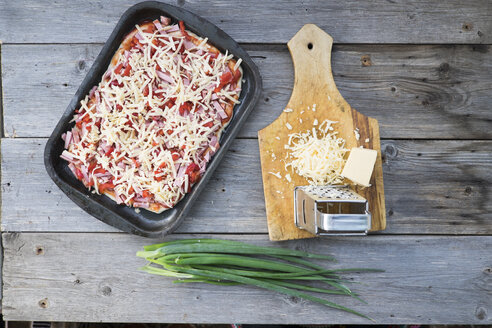 Cheese on cutting board near tray of pizza - BLEF04661
