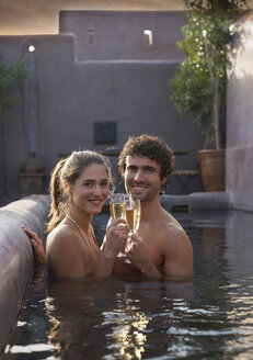 Smiling Caucasian couple toasting with champagne in swimming pool - BLEF04679