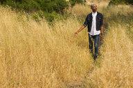 Pensive gay Black man walking in tall grass - BLEF04712