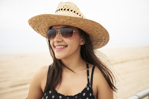 Mixed Race woman smiling on beach - BLEF04787