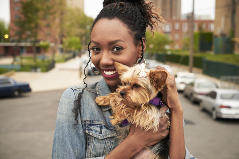 Black woman holding dog in city - BLEF04793