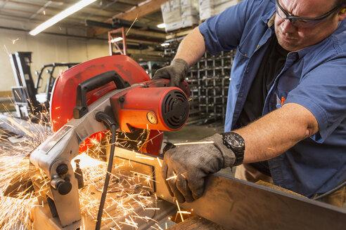 Caucasian worker cutting metal in factory - BLEF04835