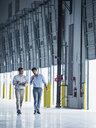 Businessmen walking with clipboard near open loading dock doors - BLEF04853
