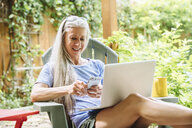 Caucasian woman cell phone and laptop on backyard patio - BLEF04904