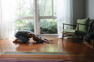 Caucasian woman kneeling on floor stretching - BLEF04928