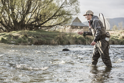 Caucasian man fly fishing in river - BLEF04973