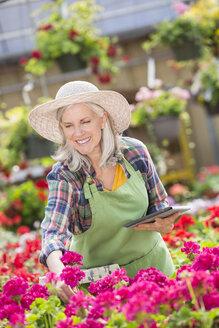 Caucasian woman using digital tablet in greenhouse - BLEF05000