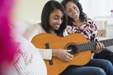 Mother watching daughter play guitar on sofa - BLEF05030