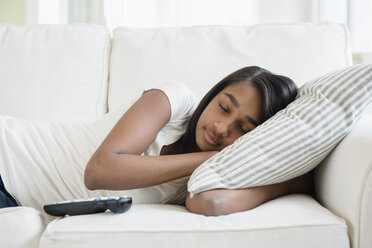 Mixed Race girl sleeping on sofa with pillow - BLEF05033