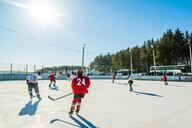 Caucasian boys playing ice hockey outdoors - BLEF05123