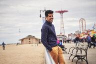 Man leaning on boardwalk railing at beach - BLEF05258