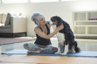 Woman on exercise mat petting dog - BLEF05279