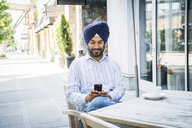 Man wearing turban texting on cell phone at cafe - BLEF05306