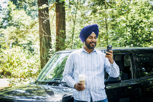 Man wearing turban posing for cell phone selfie at car - BLEF05312