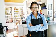 Smiling Hispanic hairdresser posing in hair salon - BLEF05381