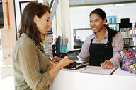 Customer paying in hair salon with cell phone - BLEF05399