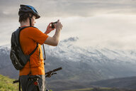 Caucasian man on mountain bike photographing scenic view - BLEF05504