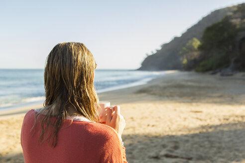 Caucasian woman drinking coffee on beach - BLEF05507