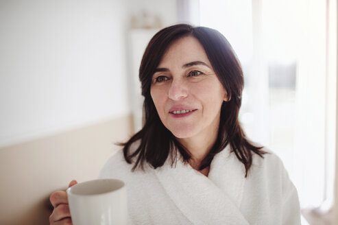 Mature woman in a bathrobe, drinking her morning coffee - HAPF02944