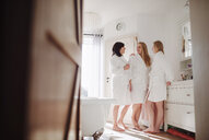 Happy mature woman with two daughters in a bathroom at home - HAPF02947