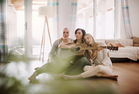 Mature woman with two daughters sitting on the floor playing guitar at home - HAPF02965