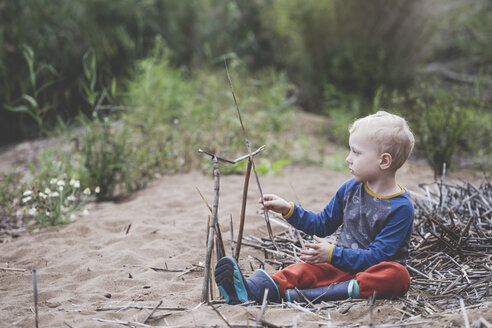 Little boy playing with sticks on the sand - IHF00045