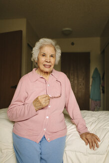 Older mixed race woman sitting on bed - BLEF05674