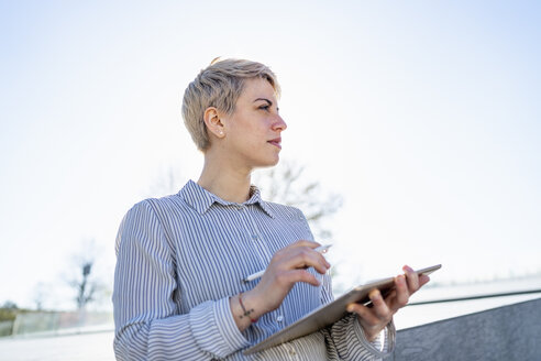 Young woman using digital tablet outdoors - FBAF00601