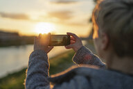 Back view of woman taking photo of sunset, close-up - FBAF00628