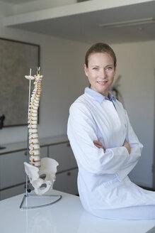 Portrait von Ärztin in Praxis mit Anatomie Model von Wirbelsäule, Studio, München, Deutschland - PNEF01465