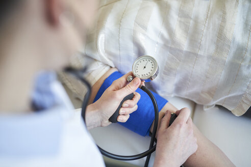 Close-up of doctor taking blood pressure of patient in medical practice - PNEF01501