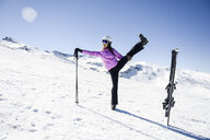Woman wearing ski clothing stretching before skiing at the Sierra Nevada, Andalusia, Spain - JSMF01096