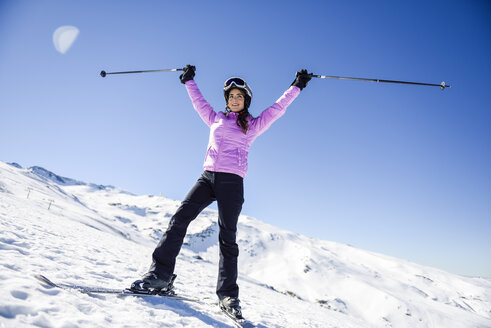 Happy woman raising her ski poles in snow-covered landscape in Sierra Nevada, Andalusia, Spain - JSMF01105