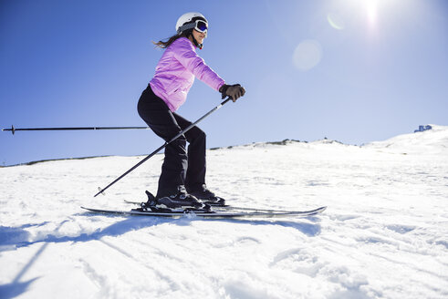 Woman skiing under blue sky, Sierra Nevada, Andalusia, Spain - JSMF01123