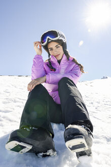 Portrait of smiling woman taking a break after skiing sitting on the snowy ground in Sierra Nevada, Andalusia, Spain - JSMF01132