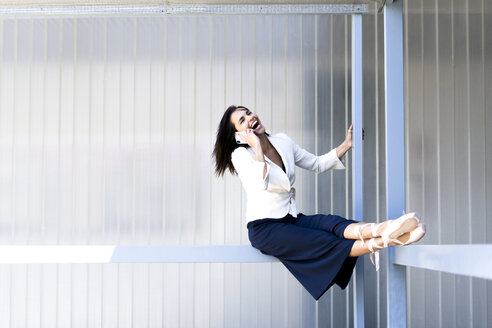 Female ballet dancer sitting on a railing, using smartphone and laughing - ERRF01445