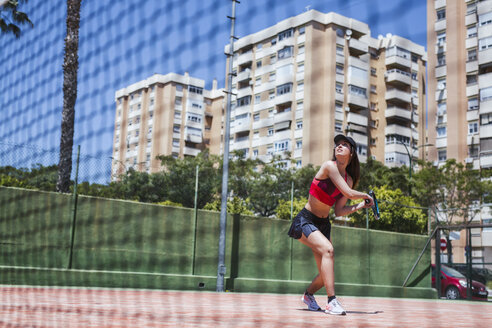 Female tennis player playing on court in the city - LJF00054