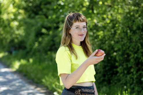 Portrait of young woman with glasses, holding an apple - FLLF00223