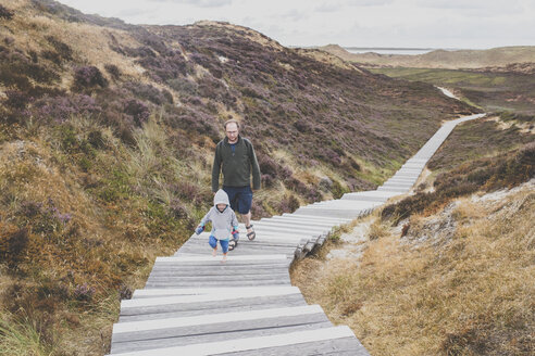 A father and a small daughter walking on a stairs among the dunes, Sylt, DE - IHF00052